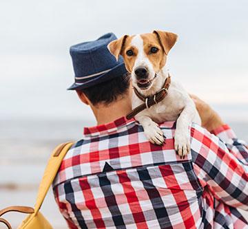 man outside holding dog
